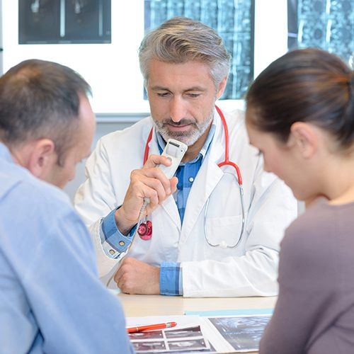 Doctor talking into dictaphone while couple look at xray results